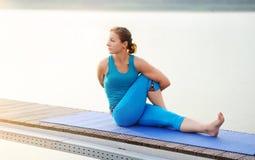 Молодая женщина делая одну усаженную ногу вращалась представление йоги Стоковые Фотографии RF