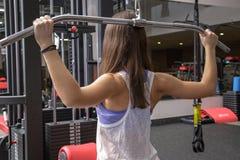 Молодая женщина делая тренировки на приборах тренировки Стоковые Фотографии RF