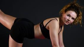 Молодая женщина делая тренировку планки на черной предпосылке видеоматериал