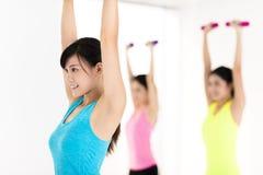 Молодая женщина делая тренировку с гантелью в спортзале стоковое изображение