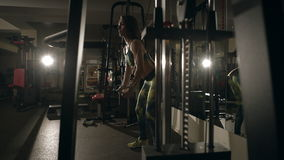 Молодая женщина делая тренировку для задней части на машине тренировки сток-видео