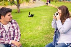 Молодая женщина делая фото к ее парню Стоковая Фотография