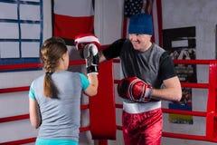 Молодая женщина делая kickboxing тренировку с ее тренером стоковые изображения rf