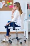 Молодая женщина дела ослабляя один момент в ее офисе Стоковые Изображения RF