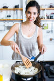 Молодая женщина жаря лук в лоток в кухне Стоковые Изображения RF