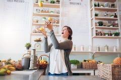 Молодая женщина жонглируя с лимоном на баре сока Стоковая Фотография