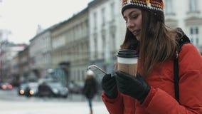 Молодая женщина ждать ее друзей outdoors и используя smartphone для отправки СМС Девушка получает сообщение на ей видеоматериал