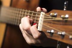 Молодая женщина зажатая с строками гитары пальцев Стоковая Фотография RF