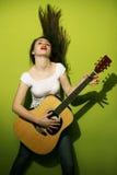Молодая женщина запальчиво играя гитару Стоковое Фото