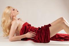 Молодая женщина задрапированная в красной ткани сатинировки Стоковые Фотографии RF