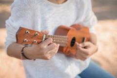 Молодая женщина играя на гавайской гитаре Стоковое Фото