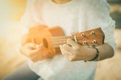 Молодая женщина играя на гавайской гитаре Стоковые Изображения