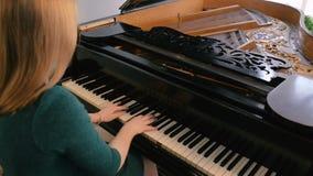 Молодая женщина играя на черном рояле акции видеоматериалы