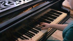 Молодая женщина играя на черном рояле видеоматериал