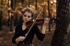 Молодая женщина играя парк скрипки осенью Стоковое Изображение RF