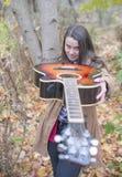 Молодая женщина играя с ее гитарой Стоковое Изображение