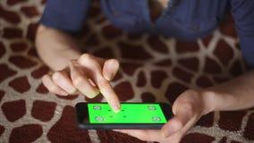 Молодая женщина играя с smartphone дома на руках экрана зеленого цвета покрывала жирафа готовых только сток-видео