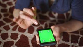 Молодая женщина играя с smartphone дома на руках экрана зеленого цвета покрывала жирафа готовых только акции видеоматериалы