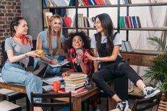 Молодая женщина изучая совместно и говоря на таблице с книгами Стоковые Фотографии RF