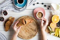 Молодая женщина имеет очень вкусный завтрак с кофе, круассанами, булочками и плодоовощами на белом деревянном столе Стоковое фото RF