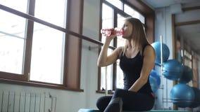 Молодая женщина имеет питьевую воду остатков в спортзале сток-видео