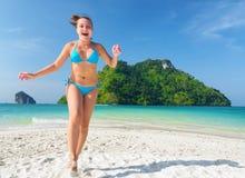Молодая женщина имеет потеху на песчаном пляже стоковое фото