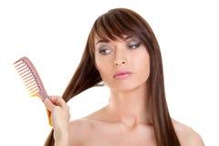 Молодая женщина имея волосы быть расчесанным Стоковое Фото