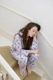Молодая женщина имея головную боль пока сидящ на лестнице Стоковое Изображение RF