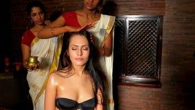 Молодая женщина имея головную обработку ayurveda Индийский женский masseuse в ayurvedic салоне курорта сток-видео