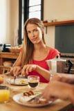 Молодая женщина имея завтрак в кухне дома Стоковые Изображения