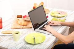 Молодая женщина имея завтрак пока использующ портативный компьютер Стоковое Изображение RF