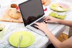 Молодая женщина имея завтрак пока использующ портативный компьютер Стоковые Изображения RF