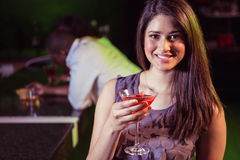 Молодая женщина имея коктеиль на счетчике бара Стоковое Изображение RF