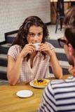 Молодая женщина имея кофе в столовой Стоковое Фото