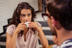 Молодая женщина имея кофе в столовой Стоковые Фото