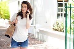 Молодая женщина имея переговор на мобильном телефоне Стоковые Фотографии RF