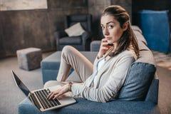 Молодая женщина имея переговор на smartphone во время работы на компьтер-книжке дома стоковое изображение