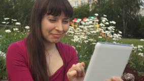 Молодая женщина использует белый планшет сидя рядом с маргаритками outdoors акции видеоматериалы