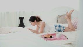 Молодая женщина используя беспроводную технологию лежа на белой кровати и беседуя дома Девушка печатая на компьтер-книжке во врем Стоковые Фото