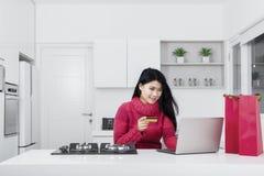 Молодая женщина используя кредит и компьтер-книжку карточки Стоковое Изображение RF