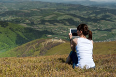 Молодая женщина используя планшет outdoors Стоковые Фото