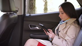 Молодая женщина используя таблетку в автомобиле видеоматериал