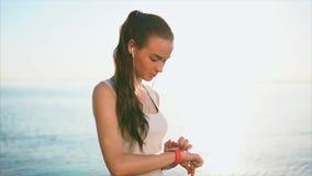 Молодая женщина используя умные вахты перед морем во время захода солнца видеоматериал