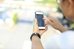 Молодая женщина используя умный телефон в городе Стоковое фото RF