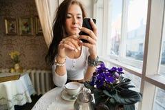Молодая женщина используя умный телефон на таблице кафа Стоковое Изображение RF