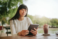 Молодая женщина используя цифровую таблетку в кафе Стоковые Изображения