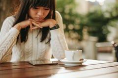 Молодая женщина используя цифровую таблетку на кафе Стоковые Изображения