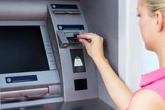 Молодая женщина используя ATM стоковые фотографии rf