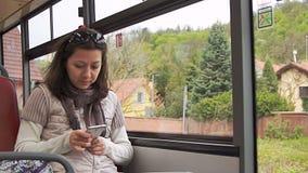Молодая женщина используя smartphone пока едущ шина сток-видео