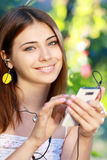 Молодая женщина используя smartphone для того чтобы слушать к музыке стоковое изображение